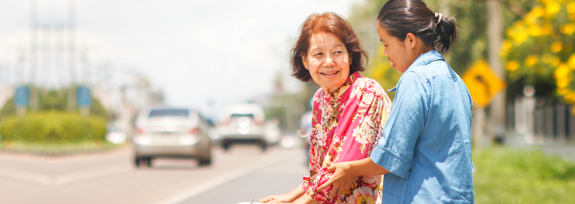 young lady assisting elderly woman in crossing the street
