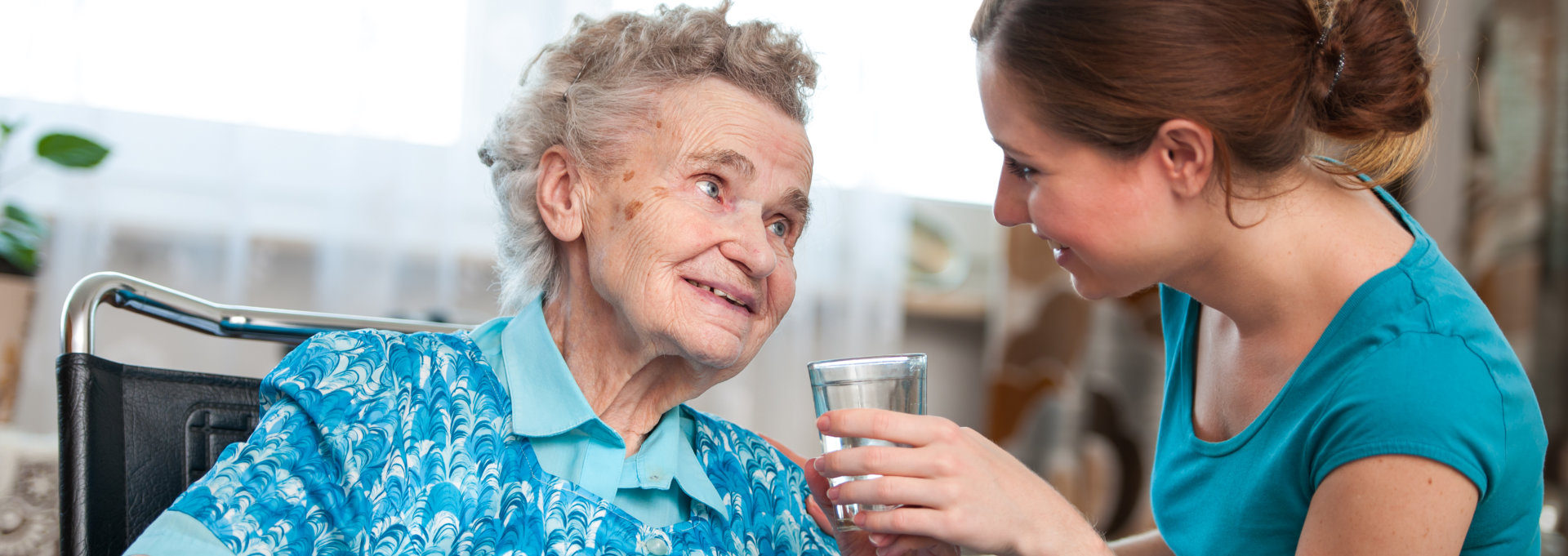 Caregiver gave water to the old woman
