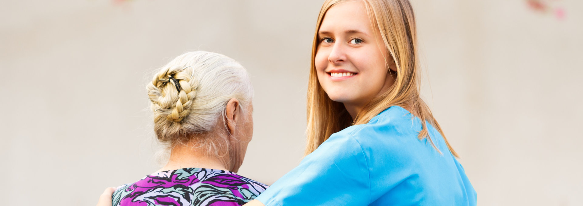 caregiver smiling with an elderly woman beside her